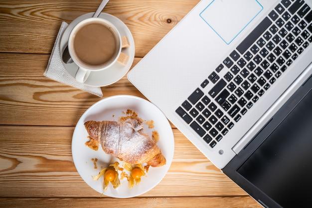 コンピューター、カップコーヒー、クロワッサンに茶色の木のテーブル Premium写真