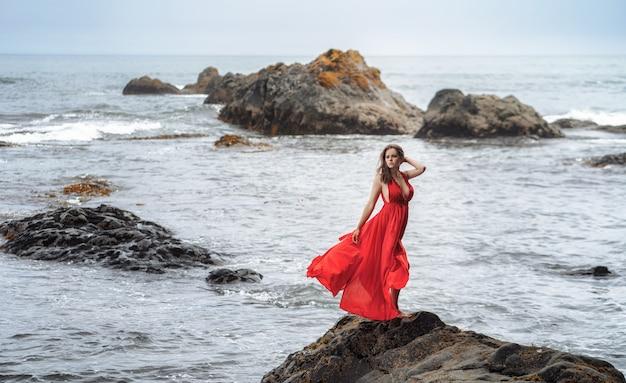 岩の上の海でポーズをとって長い赤いドレスの美しい少女 Premium写真