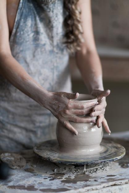 陶工は、ろくろの上に花瓶を彫る Premium写真