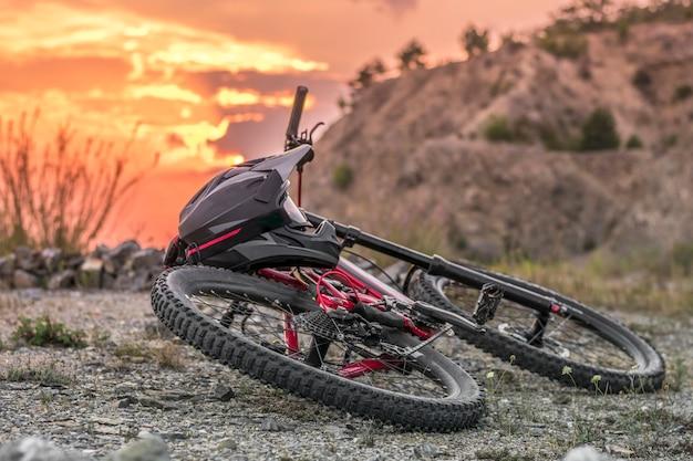 日没の黒いフルフェイスヘルメットとダウンヒルバイクのバックショット。 Premium写真