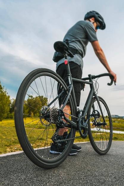 自転車道のロードバイクとサイクリストの垂直方向のショット。 Premium写真