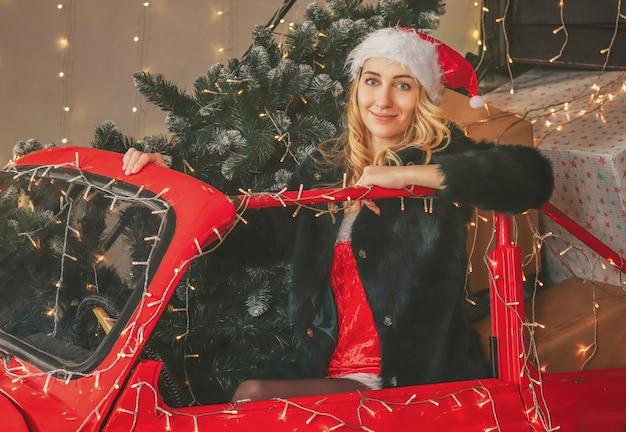 お祝いデコレーションとギフトとクリスマスツリーの赤い車の若いかなり雪の乙女 Premium写真