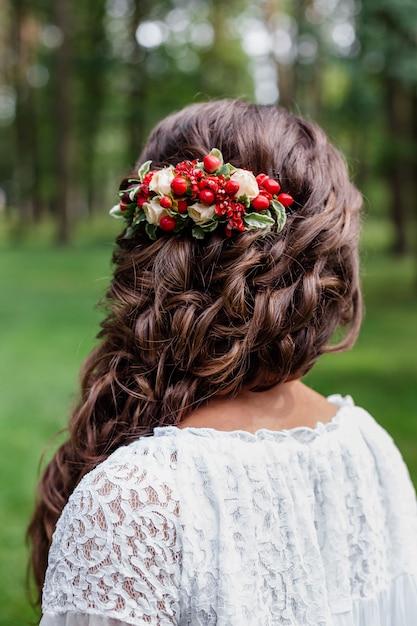 Невеста с красными живыми цветами и зеленью в волосах Premium Фотографии