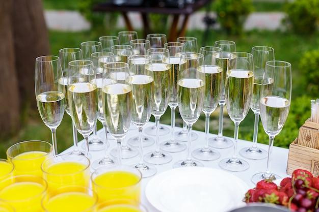 Наполненные бокалы с шампанским стоят рядами на столе. свадьба, питание на свежем воздухе. напитки, соки и фрукты - праздничный банкет, прием Premium Фотографии