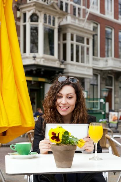 旅行ジュースオレンジイエローガールコート巻き毛タブレットヨーロッパコミュニケーションスマイルストリート古い家オランダハーグ花コーヒー太陽 Premium写真