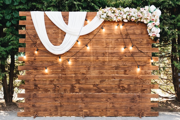 新婚夫婦の結婚式のための花で飾られたレトロなガーランドの素朴な木製の結婚式のアーチ Premium写真