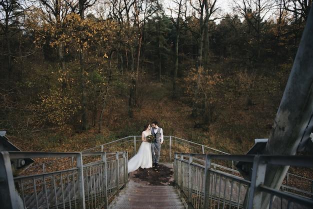 幸せな若い新郎新婦が森に架かる吊り橋の階段に立っています。結婚式の写真 Premium写真