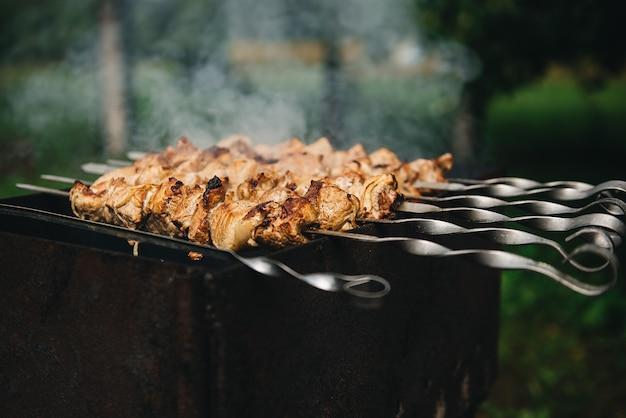 Аппетитный шашлык обжаривается на шпажках на открытом угольном гриле. шашлык с дымом Premium Фотографии