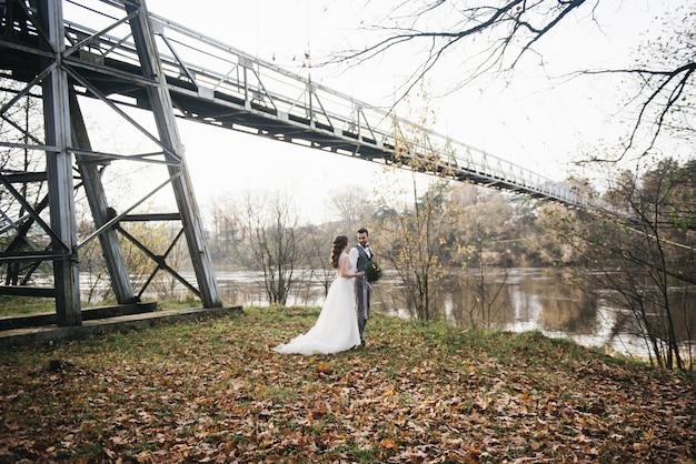 Счастливые молодые улыбающиеся жених и невеста стоят возле висячего моста и реки. свадебные фото в интересном месте Premium Фотографии