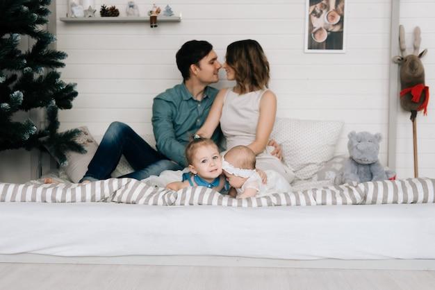 クリスマスの装飾が施された部屋で赤ちゃんと一緒に幸せな親 Premium写真