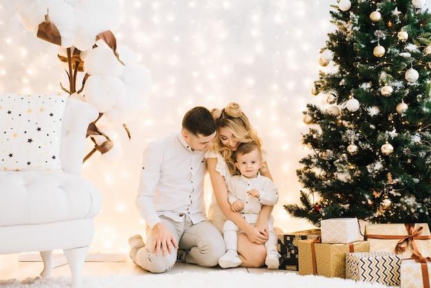 クリスマスツリーを背景に美しい若い家族の肖像画。魅力的な両親と幼い息子が新年を祝って笑顔 Premium写真