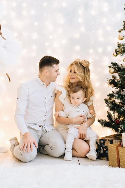 クリスマスツリーに対する美しい若い家族の肖像画。魅力的な両親と幼い息子が新年を祝って笑顔 Premium写真