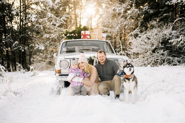 小さな子供を持つ幸せな若い家族がクリスマスの準備をして、ハスキー犬と一緒にレトロな車で、クリスマスツリーの屋根の上と冬の雪に覆われた森の中の贈り物を歩いています。 Premium写真