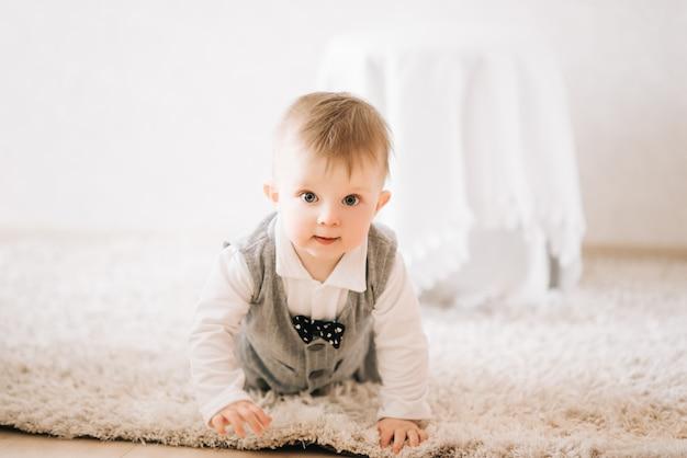 スタイリッシュな紳士スーツの家でクロールのかわいい幸せな子供 Premium写真