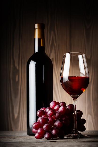 Черная бутылка и бокал красного вина с виноградом Premium Фотографии