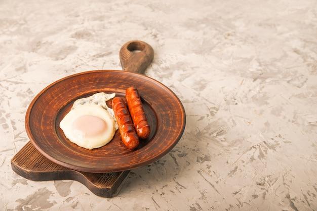 Жареные колбаски с яйцом крупным планом. Premium Фотографии