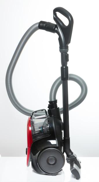 白のホースなしのコンテナーと黒と赤の掃除機 Premium写真