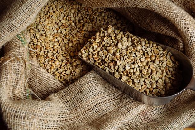 Зеленый необжаренный кофе лежит в мешковинах. Premium Фотографии