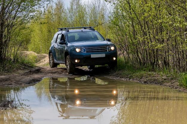 Грязный автомобиль на грязной дороге в лесу. Premium Фотографии