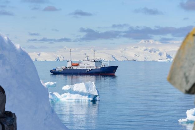 Экспедиционный корабль с айсбергом в антарктическом море Premium Фотографии