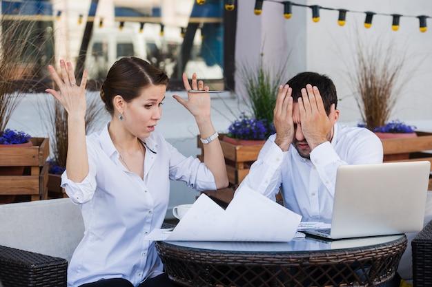 怒っている上司が同僚のビジネスマンと女性に悲鳴を上げて怒っている上司が昼休み中に屋外カフェでのレポート会議を議論する深刻な議論否定的な感情を主張する Premium写真