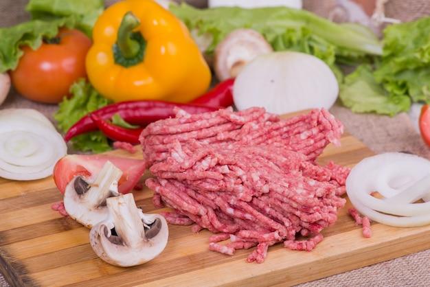 プレートとテーブルのクローズアップでの新鮮野菜の生ミンチ豚。上面図 Premium写真