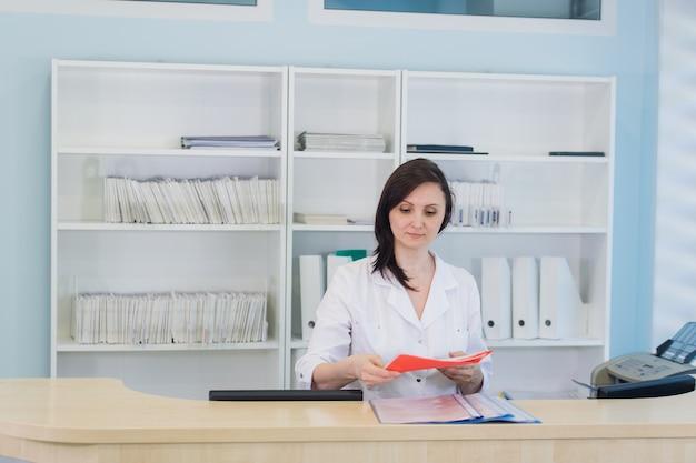 クリニックの受付で働く若い開業医医師、彼女は電話に応答し、予定をスケジュールしています Premium写真