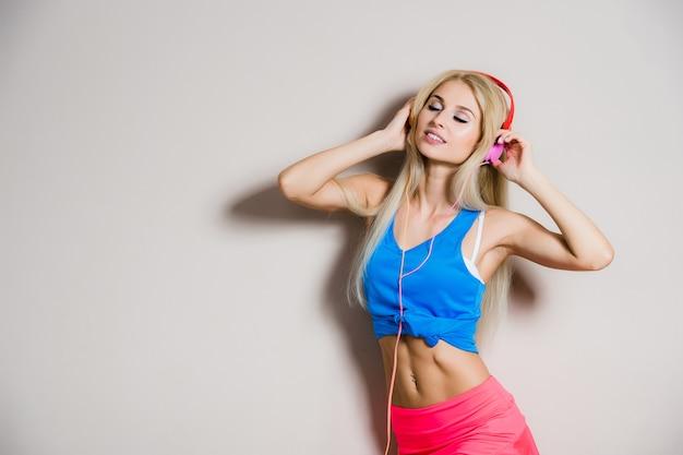 パンティーやカラフルなヘッドフォンで音楽を聞いてショートパンツを着て幸せなセクシーな女性 Premium写真