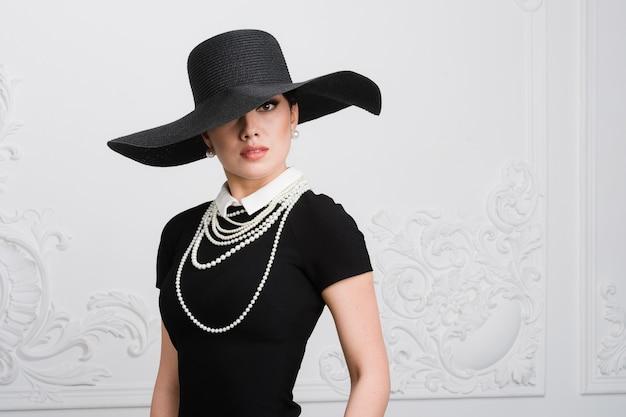 Ретро женский портрет. девушка в винтажном стиле, носящая старомодную шляпу, прическу и макияж Premium Фотографии