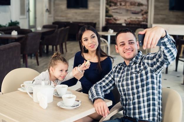 Семья, родители, технологии люди концепции - счастливая мать, отец и маленькая девочка, обедали, принимая селфи по телефону в ресторане Premium Фотографии