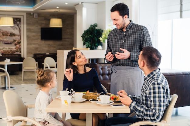 Дружелюбный улыбающийся официант принимает заказ за столом семьи, обедают вместе Premium Фотографии