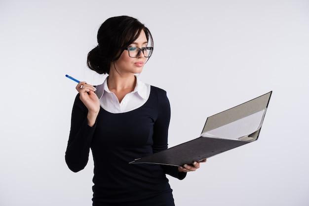 Молодая женщина кавказской носить темно-синее платье, белую рубашку, держа папку папка-переплет и ручку. Premium Фотографии