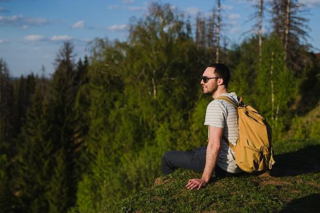 森の中で屋外のバックパックでハイキングを使用している人 Premium写真