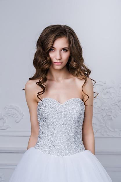 Близкий портрет красивой усмехаясь женщины невесты при длинные вьющиеся волосы представляя в платье свадьбы на интерьере и усмехаться. салон красоты крытый портрет. Premium Фотографии