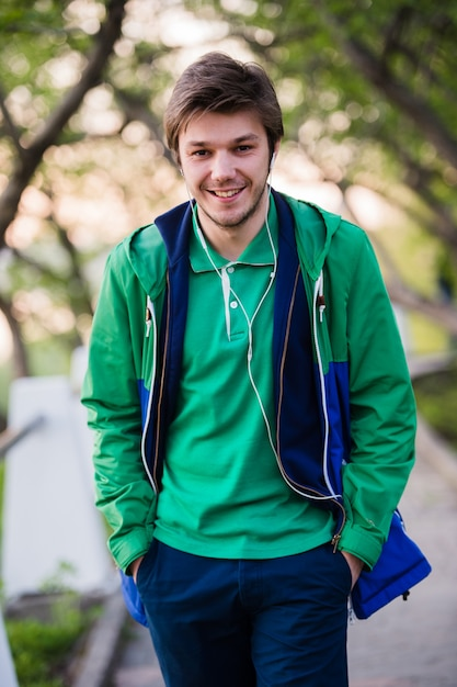 Красивый человек, прогулки по городу, улыбаясь и слушать музыку в парке. мягкий закатный свет. Premium Фотографии