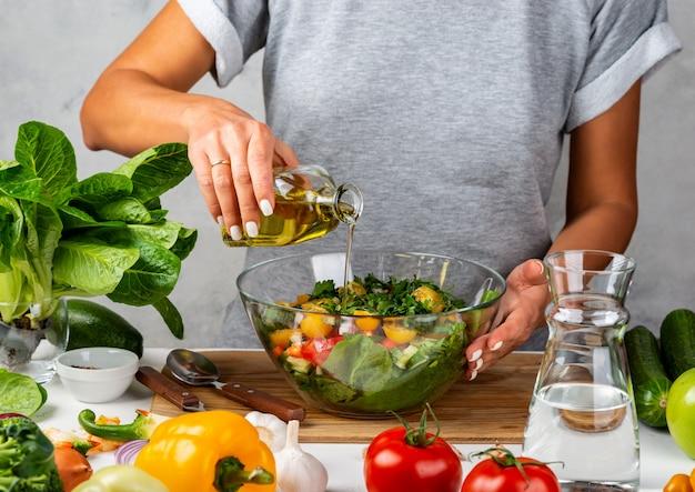 女性はボトルからオリーブオイルをガラスのボウルのサラダに注ぐ。キッチンで料理。健康的な食事のコンセプト。 Premium写真