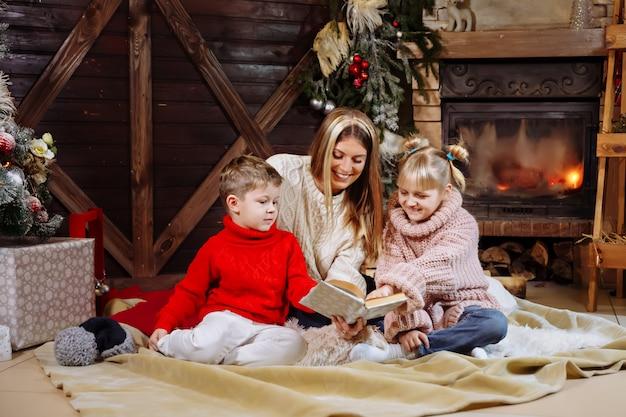 メリークリスマスと新年あけましておめでとうございます、クリスマスツリーの近くの娘と息子に本を読んでかなり若い母親。 Premium写真