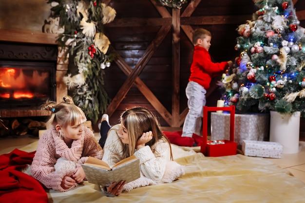 メリークリスマスと新年あけましておめでとうございます、クリスマスインテリアの美しい家族。 Premium写真
