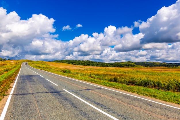曲がりくねった田舎道と曇りの青い空 Premium写真