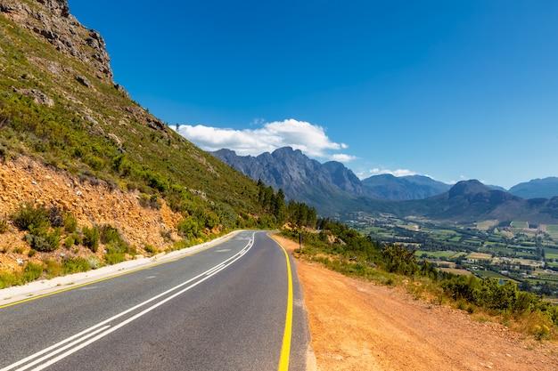 Живописная дорога в долине франшхук с ее знаменитыми винодельнями и окружающими горами, южная африка Premium Фотографии