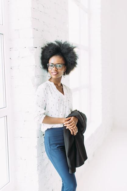 メガネ、大きな窓の近くに立って、ジャケットを保持している若いアフリカ系アメリカ人ビジネス女性 Premium写真