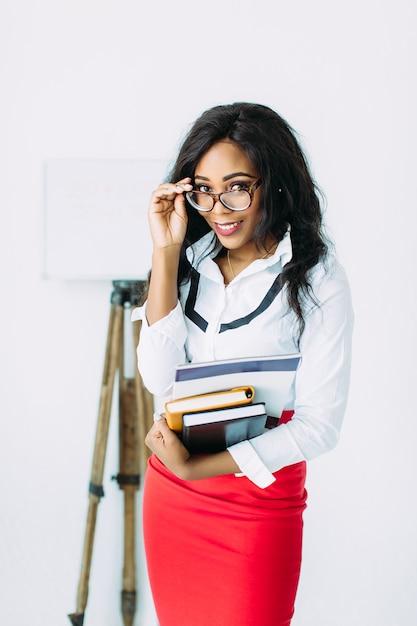 白で立って本やドキュメントを保持しているメガネのアフリカビジネス女性 Premium写真