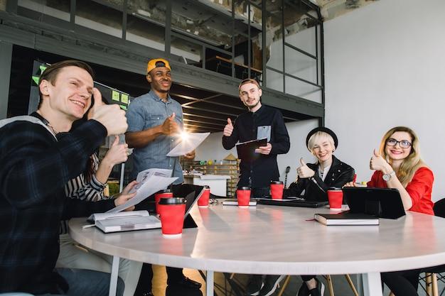 創造的なアイデアを議論するグループの若いビジネス人々が集まった。コーヒーとコンピューターのテーブルに座って話している留学生のグループ Premium写真