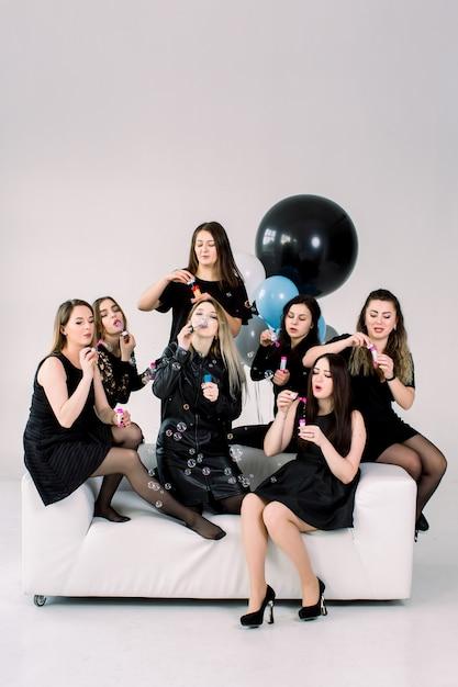 誕生日や鶏のパーティーを祝って、屋内の白いソファに座って、シャボン玉を吹いて幸せな美しい女性。誕生日パーティー、風船、休日 Premium写真