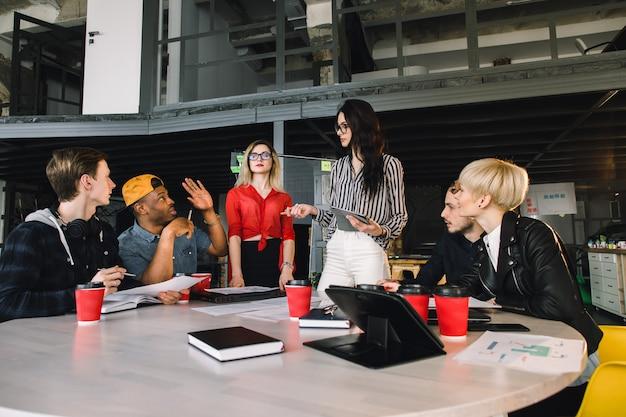一緒に働く幸せな同僚の多民族の多様なグループ。クリエイティブチーム、カジュアルなビジネス同僚、または近代的なオフィスでのプロジェクト会議の大学生。スタートアップまたはチームワークの概念 Premium写真