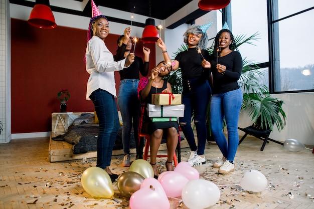Африканские друзья празднуют день рождения и держат бенгальские огни и шляпы и подарки Premium Фотографии