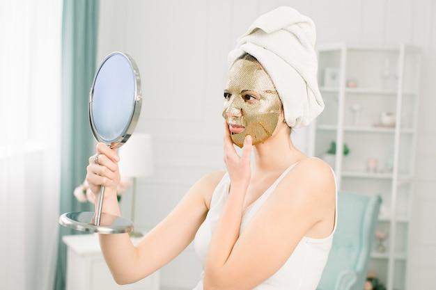 Уход за кожей лица и косметические процедуры. женщина с листовой увлажняющей золотой маской на лице и белым полотенцем на голове, смотрит в зеркало. Premium Фотографии