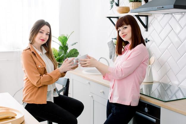 Пара лесбиянок-девчонок наслаждайтесь кофе дома, принимая что-нибудь две молодые взрослые красивые женщины пьют чай в современном интерьере кухни белого цвета Premium Фотографии