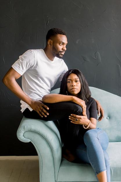 若い黒人男性と青いソファーに座っていた暗い背景にアフロアメリカンの女の子。若い男性と女性のスタジオでのファッションの肖像画 Premium写真