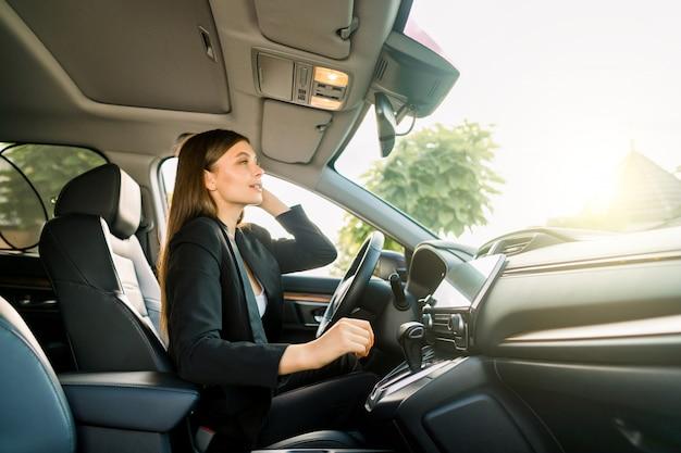 車のバックミラーを見て黒いスーツを着たジョージの若いビジネス女性。バックミラーで自分を探している若い笑顔実業家。側面図 Premium写真